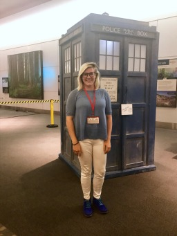 Kelly standing in front of a life-size Tardis (blue Police Box)